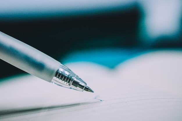 Zamyka w górę ręki używać pióra writing na notatniku
