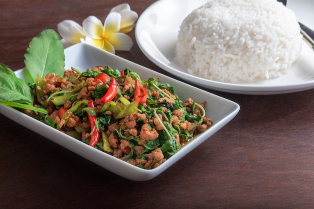 Zamyka w górę rice z smażącą wieprzowiną z basilu liściem w białym naczyniu na ciemnego brązu stole