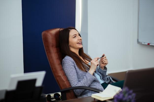 Zamyka w górę rozważnej młodej biurowej kobiety relaksuje przy jej biurkiem z rękami za jej głową i przyglądający up.