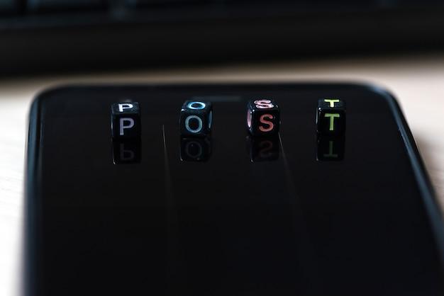 Zamyka w górę słów post na blokach na czarnym mądrze telefonie na biurku