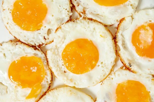 Zamyka w górę smażących jajek na prostym tle