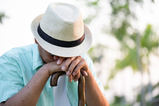 Zamyka w górę smutnego starszego azjatykciego starego człowieka gubiącego w myśli siedzi w parku