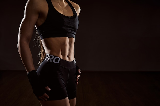 Zamyka w górę sportowej kobiety z abs. młoda kobieta kulturysta z silnymi mięśniami brzucha pozowanie.