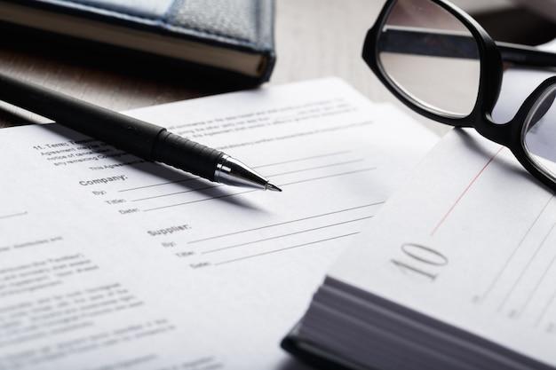 Zamyka w górę strzału eyeglasses na dokumencie tapetuje biznesowego pojęcie