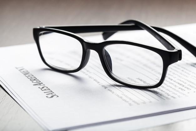 Zamyka w górę strzału eyeglasses na kontraktacyjnym dokumencie tapetuje biznesowego pojęcie