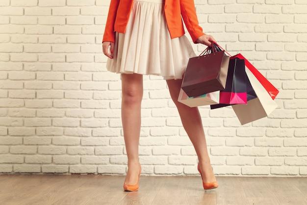 Zamyka w górę strzału młodej kobiety noga niesie kolorowych torba na zakupy