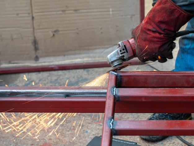 Zamyka w górę strzału pracownika szlifierskiego metalu i spawu metalu z wiele pożarniczymi iskrami