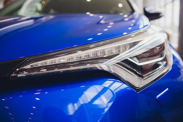 Zamyka w górę strzału reflektoru w luksusowym błękitnym samochodzie. nowoczesna i droga koncepcja samochodu sportowego