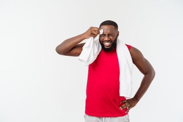 Zamyka w górę strzału smutny zmęczony amerykanina afrykańskiego pochodzenia mężczyzna wyciera twarz z białym ręcznikiem na bielu w sportswear