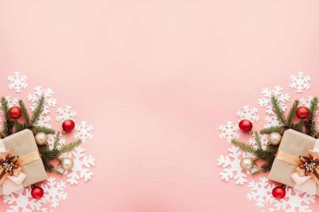 Zamyka w górę strzału zawijającego z faborkiem na różowym tle mały prezent. boże narodzenie minimalna koncepcja.