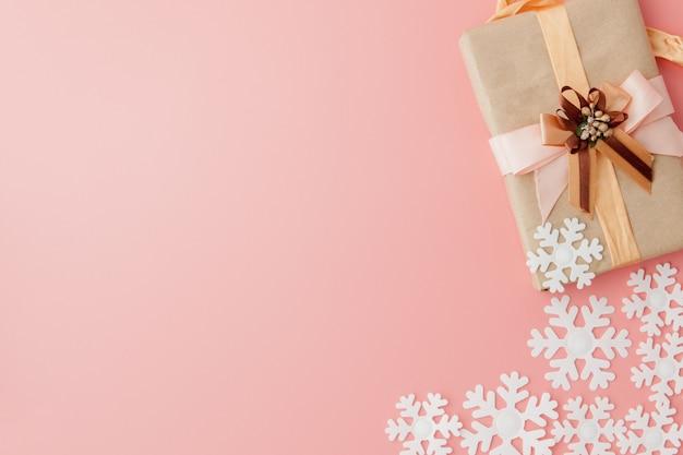 Zamyka w górę strzału zawijającego z faborkiem na różowym tle mały prezent.