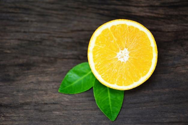 Zamyka w górę świeżej pomarańczowej plasterek połówki i pomarańczowego liścia owoc zdrowego pojęcia - pomarańczowa owoc na drewnianym stole