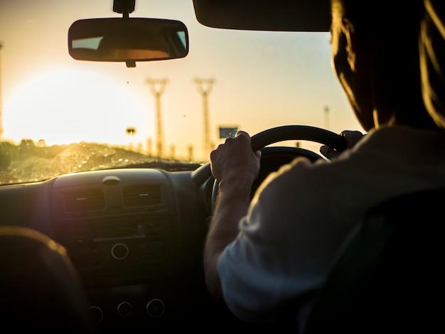 Zamyka w górę sylwetki mężczyzna jedzie samochód na zmierzchu podczas złotej godziny