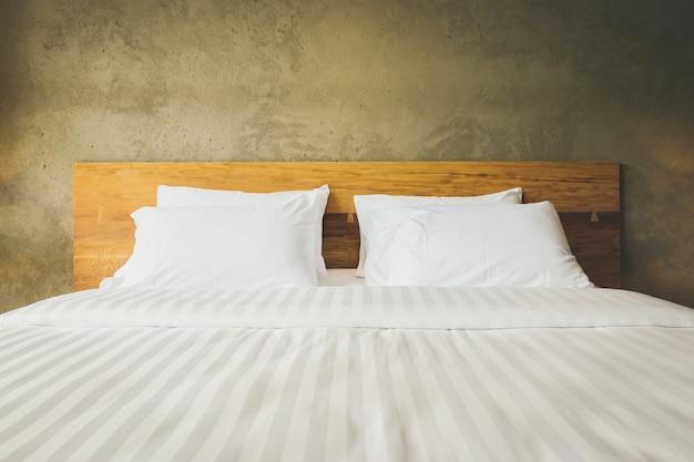 Zamyka w górę sypialnia apartamentu wnętrze z białymi poduszkami i ściana betonu tłem