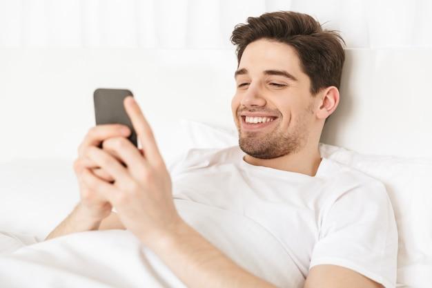Zamyka w górę szczęśliwego młodego człowieka lying on the beach w łóżku