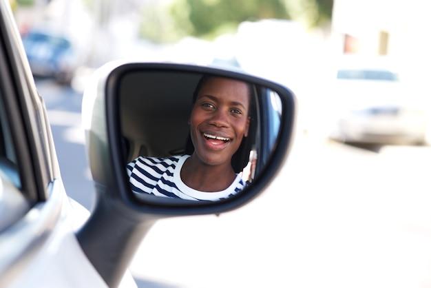 Zamyka w górę szczęśliwej afrykańskiej kobiety napędowego samochodu i patrzeje w strony lustrze