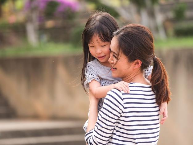 Zamyka w górę szczęśliwej małej dziewczynki twarzy w jej matek rękach.