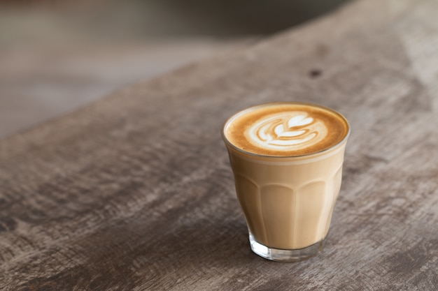 Zamyka w górę szklanej filiżanki latte sztuki kawa na drewnianym stole