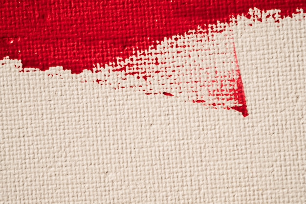 Zamyka w górę tekstura czerwonego koloru farby na białym brezentowym tle