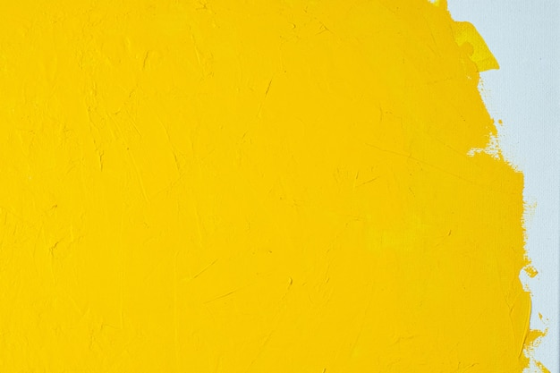 Zamyka w górę tekstury żółtego koloru farby na białym koloru kanwie szczotkuje znaki uderzenia tło