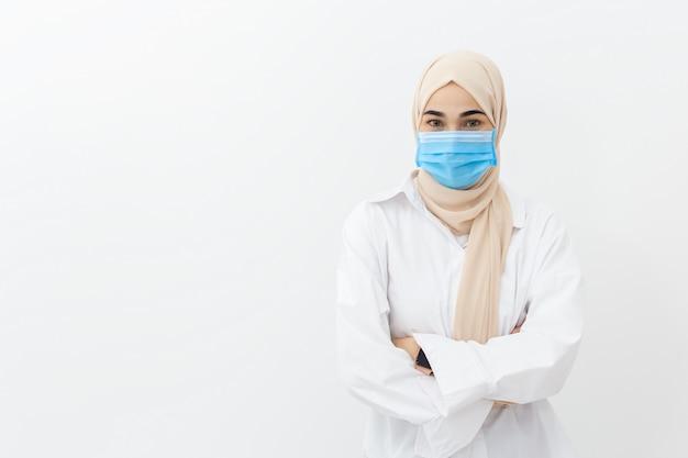 Zamyka w górę twarzy muzułmańskiej kobiety jest ubranym medyczną maskę dla zapobiega infekcja wirusa na biel ścianie, coronavirus (covid-19) pojęcie.