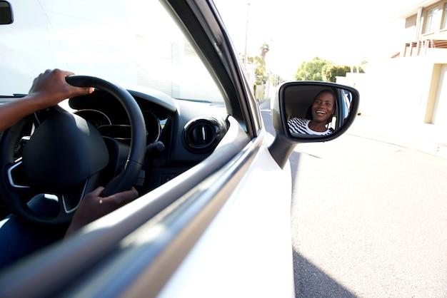 Zamyka w górę uśmiechać się czarnego napędowego samochód i patrzeć w bocznym lustrze