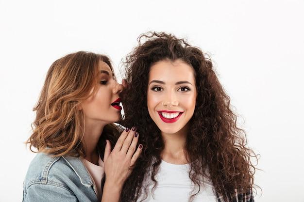 Zamyka w górę uśmiechniętej kędzierzawej dziewczyny patrzeje kamerę podczas gdy jej przyjaciel opowiada ona w ucho nad biel ścianą