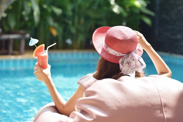 Zamyka w górę widoku atrakcyjna młoda kobieta relaksuje na zdroju pływackim basenie. podróż, emocje szczęścia, koncepcja wakacji letnich.
