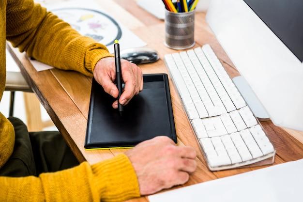 Zamyka w górę widoku biznesmen używa pastylki grafikę w jego biurze
