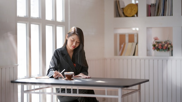 Zamyka w górę widoku bizneswomany pracuje na cyfrowej pastylce w nowożytnym miejscu pracy