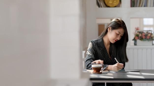 Zamyka w górę widoku bizneswomany pracuje na cyfrowej pastylce w wygodnym miejscu pracy