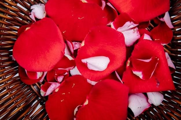 Zamyka w górę widoku czerwieni róży kwiatu płatki w łozinowym koszu