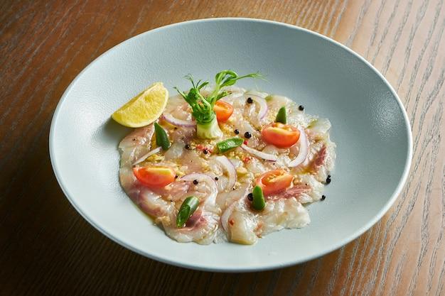 Zamyka w górę widoku dennego basu ceviche słuzyć w białego pucharu drewnianym tle. świeży i smaczny cebiche. surowa ryba. kuchnia ameryki łacińskiej. ziarno hałasu na słupku