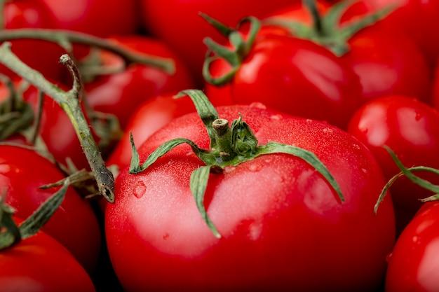 Zamyka w górę widoku dojrzali świezi pomidory z wodnymi kroplami