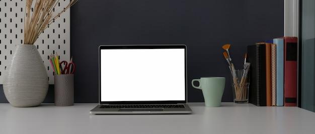 Zamyka w górę widoku domowego biura biurko z laptopem, dekoracjami i dostawami pustego ekranu