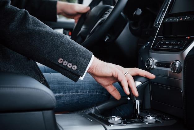 Zamyka w górę widoku dorosła osoba zmienia przekładnię w luksusowym nowym samochodzie