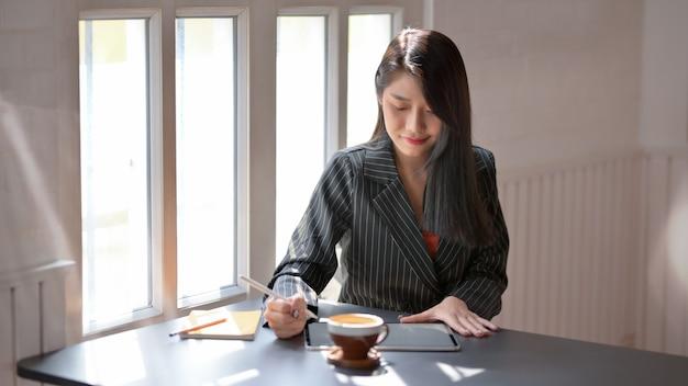 Zamyka w górę widoku kobieta używa cyfrową pastylkę w wygodnym miejscu pracy
