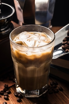 Zamyka w górę widoku kostki lodu w zimnej warzącej kawie w szkle na ciemnej przestrzeni