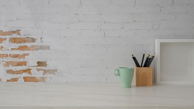 Zamyka w górę widoku miejsce pracy z kubkiem, makiety ramą, materiały i kopii przestrzenią na marmurowym biurku