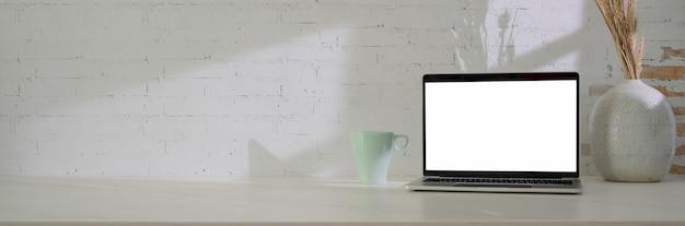 Zamyka w górę widoku minimalny workspace z pustego ekranu laptopem, kubkiem, dekoracją i kopii przestrzenią na bielu stole ,.