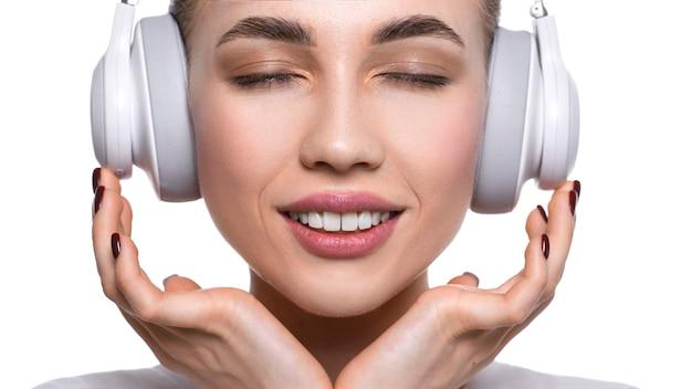 Zamyka w górę widoku młoda kobieta słucha muzyka przez hełmofonów. pojedynczo na białym