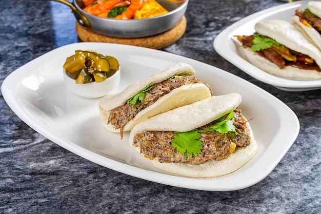 Zamyka w górę widoku na bao z wołowina policzkiem. gua bao, bułeczki na parze podawane na białym talerzu. tradycyjne tajwańskie jedzenie gua bao na marmurowym stole. azjatycka kanapka gotowana na parze. azjatyckie fast foody