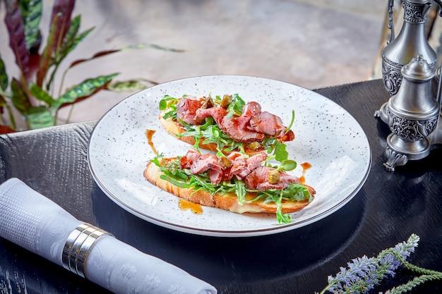 Zamyka w górę widoku na ciabatta z pieczoną wołowiną i rukolą słuzyć na bielu talerzu. jedzenie w restauracji. przekąska na lunch kuchnia włoska. soczysta kanapka ze stekiem.