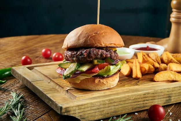 Zamyka w górę widoku na hamburgerze z francuzem smaży na rzemiosło brown papierze. tradycyjne fast foody. świeży smaczny hamburger z sałatą, pomidorem, serem i ogórkiem. skopiuj miejsce na projekt. niezdrowe jedzenie. gruby