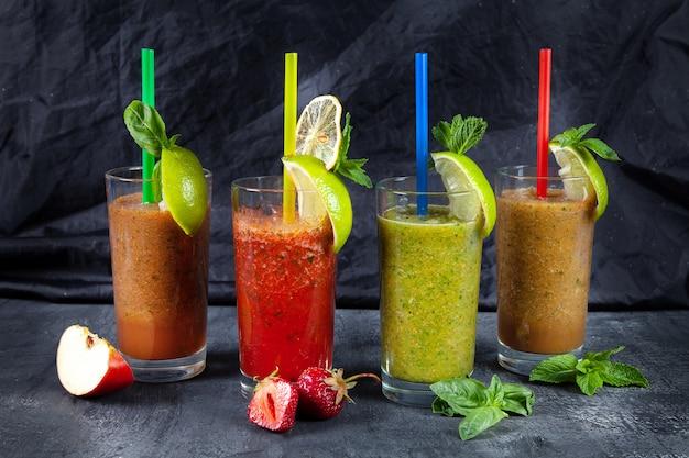 Zamyka w górę widoku na różnym secie smoothie na ciemnym tle. zdrowe koktajle ze świeżych owoców i warzyw z różnorodnymi składnikami w szkle.