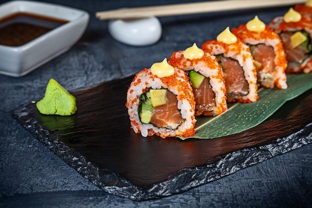 Zamyka w górę widoku na secie suszi rolka. california roll z łososiem, awokado i kawiorem podawane na czarnym kamieniu na ciemnym tle. kuchnia japońska. skopiuj miejsce podawane sushi do menu. zdrowe jedzenie, owoce morza