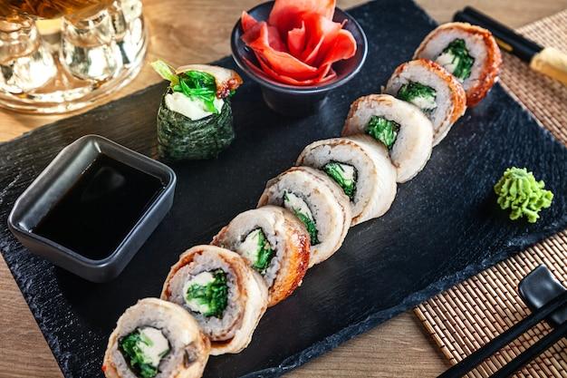 Zamyka w górę widoku na secie suszi rolka. california roll z węgorzem, awokado i kawiorem podawane na czarnym kamieniu na drewnianym stole. kuchnia japońska. skopiuj miejsce podawane sushi do menu. zdrowe jedzenie, owoce morza
