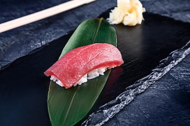 Zamyka w górę widoku na słuzyć nigiri z tuńczykiem na zmroku talerzu na zmrok powierzchni