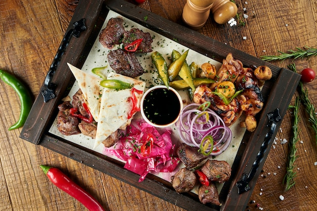Zamyka w górę widoku na smakowitym piec na grillu mięsie z warzywami na georgian pita. szaszłyk lub mięso z grilla na picie. szaszłyk, tradycyjne potrawy kuchni gruzińskiej. skopiuj miejsce na projekt. drewniana powierzchnia