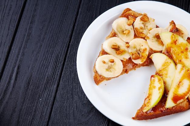Zamyka w górę widoku na śniadaniowej słodkiej grzance z bananem i jabłkiem nalewał z karmelem na ciemnym tle z kopii przestrzenią. kanapka jedzenie na śniadanie.